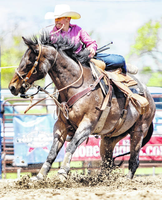 Cade Cummings dismounts during a tie-down roping competition.