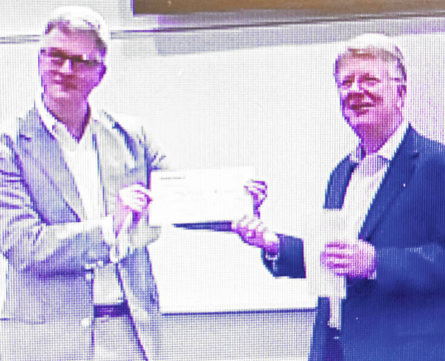 In this screen shot, David Little (left) managing director of Innergex Renewable Development USA, presents a $60,000 check to Dr. Kevin Boys, president of Southern State Community College, during a Wednesday event.