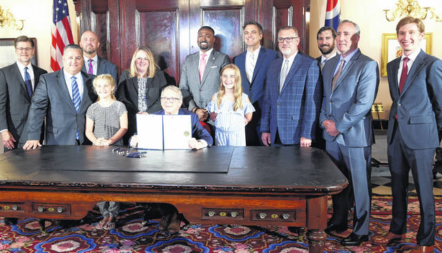 Shane Wilkin (second from left) is pictured with his daughters on either side of Ohio Governor Mike DeWine (seated).