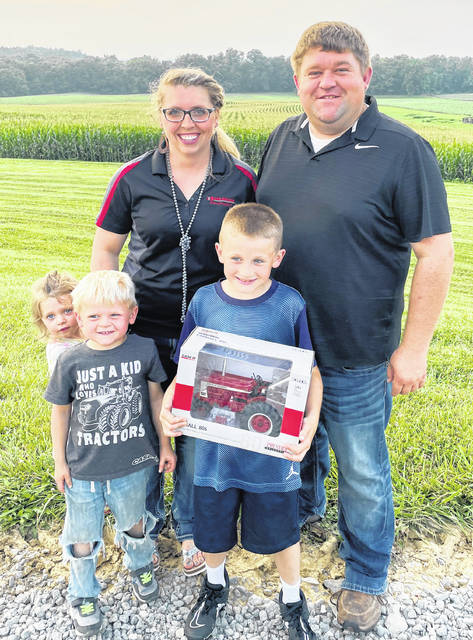 Austin Bohrer is pictured holding the 806 Case IH toy tractor he won.