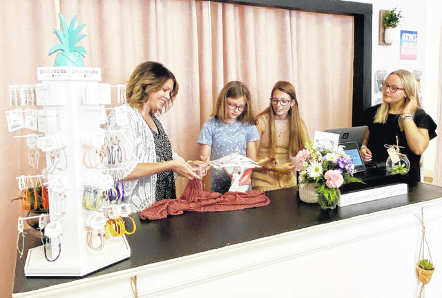 Ashely Karnes (left) preps an item for a shopping bag with the help of daughter Brynlee, niece Kyndall and family friend Shelbee, who all lend a hand in the Greenfield shop.