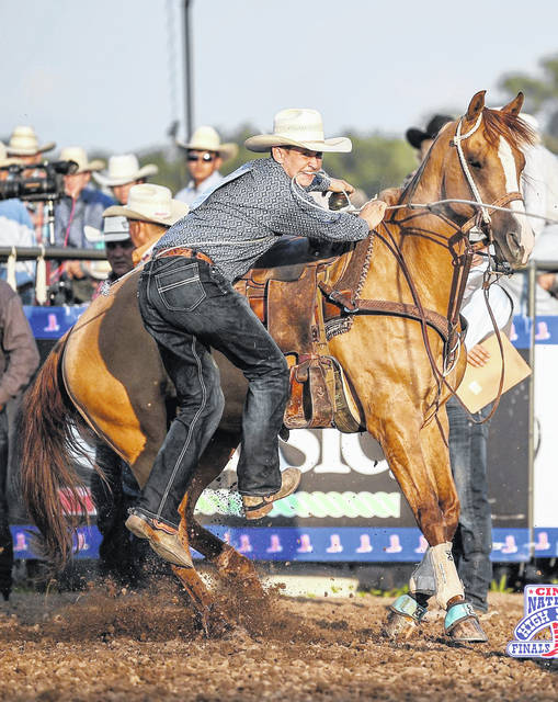 Evan Corzatt dismounts his horse and eyes a calf during the National High School Finals Rodeo in Lincoln, Nebraska.