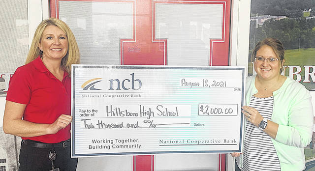 NCB's Heather Cummings (left) and Hillsboro High School's Rachel Bohrer, hold a $2,000 check for grant technology that NCB recently presented to the school.