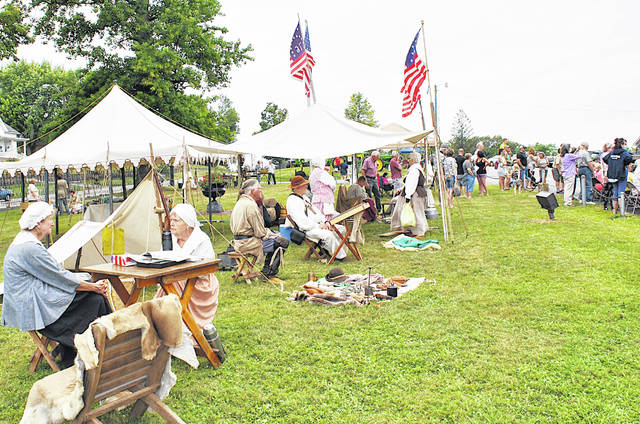Representatives from the Grassy Run Historical Arts Committee and several visitors are pictured Saturday at the second Pioneer Day hosted by the Highland County Historical Society at the Scott House in Hillsboro.