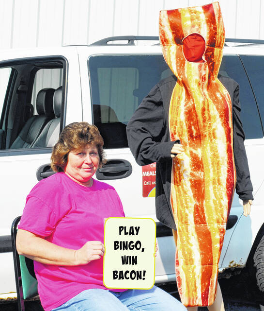 Highland County Senior Citizens Food Service Director Rhonda Purdin holds a sign promoting the center's upcoming Bacon Bingo event while someone dressed as a piece of bacon stands nearby.