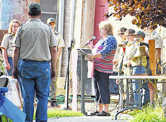 Highland County Historical Society member and event chair Jean Fawley speaks to the crowd as Boy Scouts stand at attention during Saturday's annual Log Cabin Cookout hosted by the historical society.