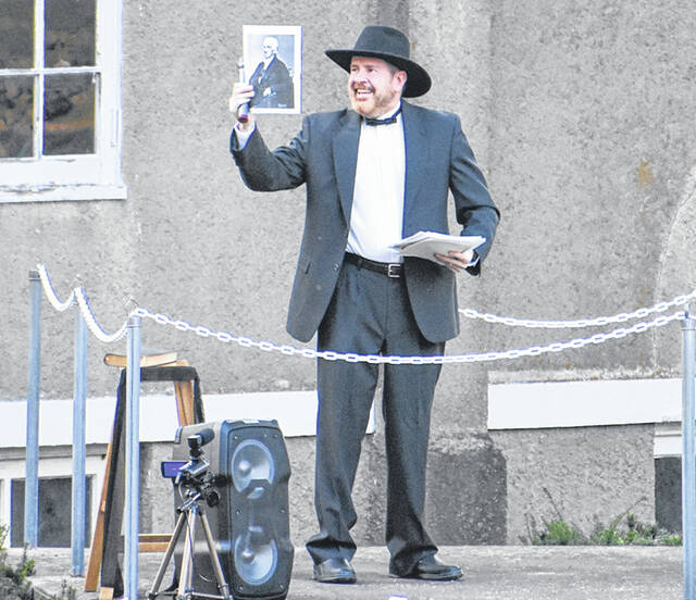 Highland County Coroner M.D. Jeff Beery holds a picture of George Beecher, the person he portrayed at Tuesday's HCHS Ghost Walk.