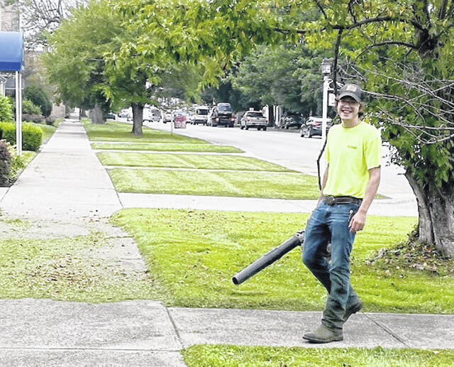 Zachary Carter blows leaves while working for Pohlman Lawncare, his Supervised Agricultural Experience project.