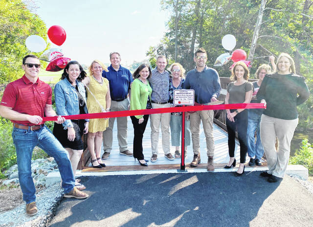 """City of Hillsboro officials and employees celebrated the grand opening of the pedestrian bridge that connects Richard Shaffer and Liberty parks with a ribbon-cutting with the Highland County Chamber of Commerce on Tuesday. Located at 1484 N. High St. in Hillsboro, the bridge offers an easy and safe passage between the two parks located at the north end of town. """"The pedestrian bridge is the final piece of the puzzle to join downtown Hillsboro by sidewalks and trails to Liberty Park. We are really glad to have this addition to our city as it lets our citizens easily enjoy our parks,"""" Hillsboro Mayor Justin Harsha said."""