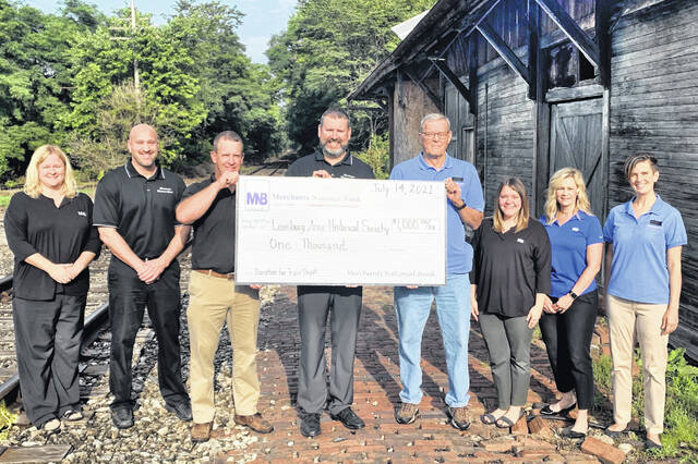 """The Leesburg Area Historical Society has announced it received a $1,000 donation toward its depot restoration project from Merchants National Bank. According to Denise Fauber, MNB vice president of branch administration and human resources, """"a goal of Merchants National Bank is to invest in our communities. The Leesburg Area Historical Society allowed us to do just that by envisioning the rich tradition, importance and legacy of the depot. We are honored to support the society with this project and are excited to see the depot come back to life."""" Pictured at the presentation of the check (l-r), are Beth Roehm, commercial/ag loan officer; Chad Hamilton, residential loan officer; Ryan Corzatt, commercial/ag loan officer; Blain Bergstrom, regional loan manager; Kenny Worley, Leesburg Area Historical Society president; Ashley Taylor, customer service representative; Denise Fauber, vice president, branch administration and human resources; and Nicole Friend, LAHS fundraising chair."""