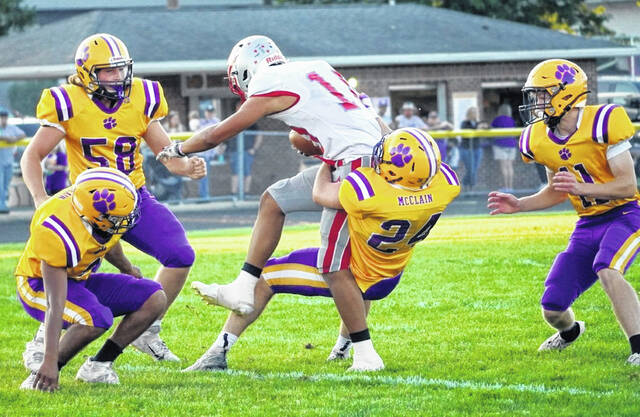 McClain's Emerson Yates (24) drags down an East Clinton ball carrier while teammates Isaac Smith (58) and Max Eichenberger (11) converge in the play.