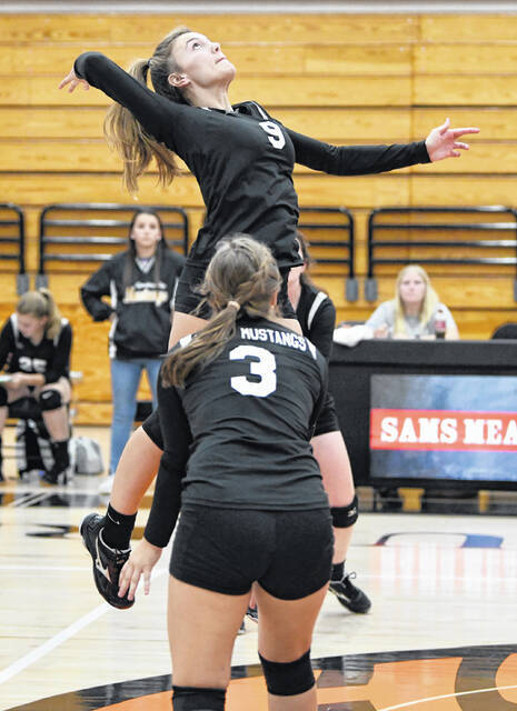 Lynchburg-Clay's Lainie Lunsford (9) goes up for a spike during a match last week at Wilmington while teammate Bell Vesey looks on. The Lady Mustangs lost to the Lady Hurricane in three games, 25-15, 25-15 and 25-13.