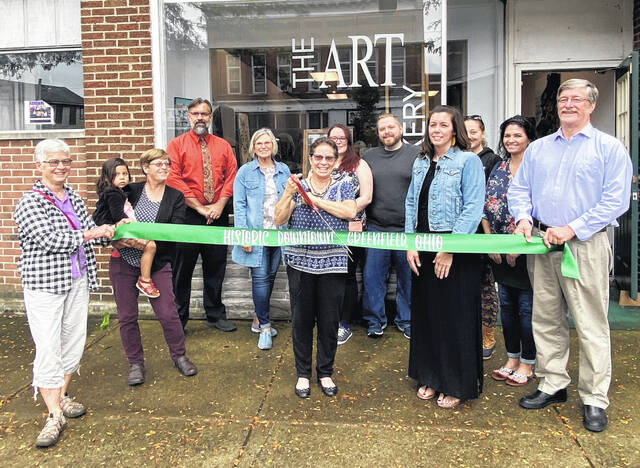 Nancy Crawford of The Art Rookery cuts the ribbon at Tuesday's event. She is surrounded by friends and family as well as Greenfield City Manager Todd Wilkin (left side in the background), Susan Howland with Greenfield (second from right), and Jamie Wheeler, executive director of the Highland County Chamber of Commerce (right of Crawford).
