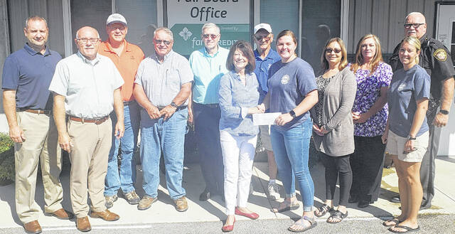 """The Highland County Republican Party and county office holders presented a donation to the Highland County Jr. Fair Board on Sept. 2. """"The donation will be used on a project to benefit the fair kids,"""" Jr. Fair Coordinator Jana Holbrook said. Paige Teeters, president of the Jr. Fair Board, is shown accepting the donation from Paulette Donley, executive chair of the local Republican Party. Pictured (l-r) are Chris Fauber, county engineer; Ike Hodson, clerk of courts; Dave Daniels, commissioner; Jeff Duncan, commissioner; Bill Fawley, auditor; Donley; Chuck Emery, party co-treasurer; Teeters; Anneka Collins, prosecuting attorney; Vicki Warnock, treasurer; Holbrook; and Donnie Barerra, sheriff. Contributing, but not present, were Dr. Jeff Beery, coroner; Terry Britton, commissioner; Chad McConnaughey, recorder; Kevin Greer, probate/juvenile judge; Bob Judkins, Highland County Court judge; and Bob Peterson, state senator."""
