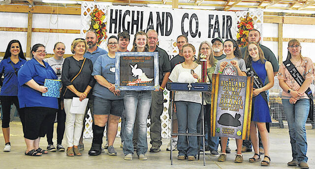 Sydney Hooper's Reserve Grand Champion Rabbit sold for $1,100 Thursday at the Highland County Fair. Hooper is pictured with the buyers, whose names were not available at press time. The buyers will be named in The Times-Gazette's upcoming Fair Memories publication.