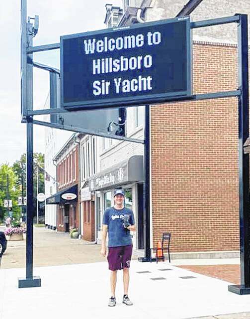 """""""Sir Yacht"""", aka Joey Knisley, is pictured beneath a sign in front of the Colony Park welcoming him to Hillsboro."""