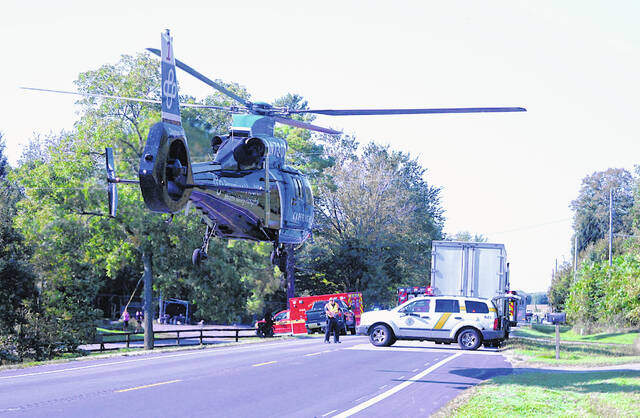 A CareFlight helicopter prepares to land Wednesday at the site of a two-vehicle accident on U.S. Route 62 south of Hillsboro.