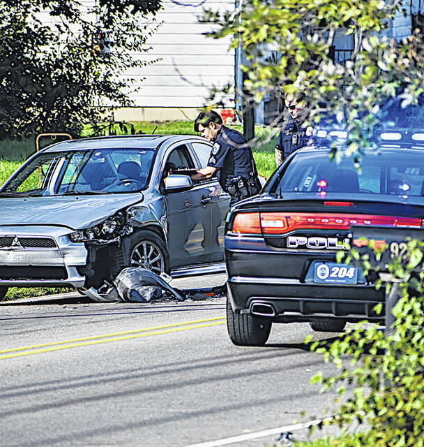 Officers with the Hillsboro Police Department investigate an automobile collision in the 900 block of North High Street on Wednesday.