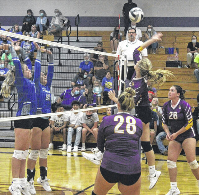 McClain's Abby Atkinson takes a swing against Washington as teammates Madi Sykes (28) and Lily Barnes (26) look on.