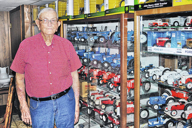 New Market area resident Jim Walker stands next to one of the toy tractor displays in his basement.