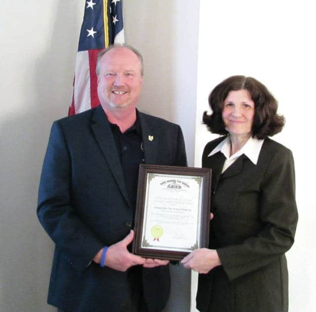 Greenville City School District (GCSD) Treasurer Carla Surber (right), and her department, earned the Auditor of State Award with Distinction. The award is a result of a recent financial audit of the GCSD by the state. Pictured is West Regional Liaison for the Auditor of State Dave Yosts's Office Joe Braden presenting the award to Carla Surber at the GCSD Board of Education Meeting May 18.