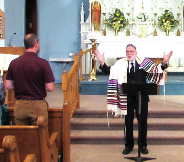 "St. Paul's Lutheran Church Pastor Peter Menke presented "" We Dare not Forget,"" an educational program about the Holocaust, at St. Mary's Catholic Church, in Greenville, June 20. Menke began the presentation by putting on a Jewish Prayer Shawl and a Kippah, small head covering."