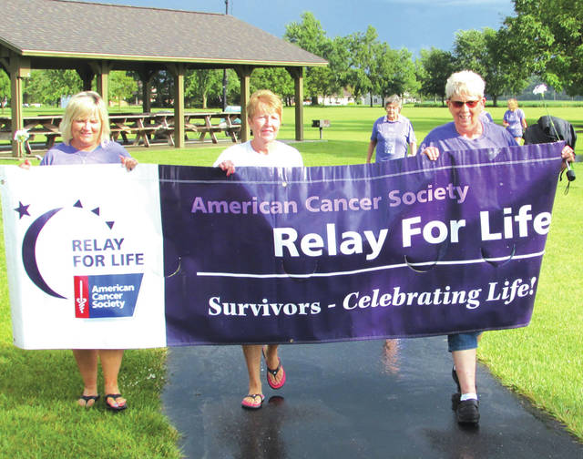 Cancer survivors take a lap at the 13th annual Relay for Life, held Friday and Saturday in Versailles. The survivors were joined by caregivers and volunteers to raise money for cancer research and treatment.