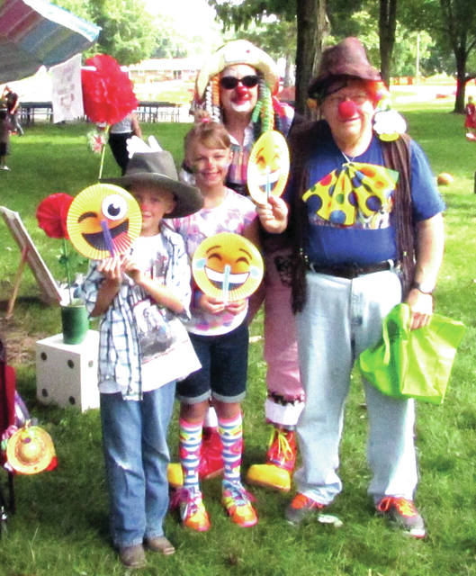 """Greenville City Park looked like a carnival Monday, with games, prizes, clowns, face - painting, kickball, cornhole music and food during """"Funday Monday"""". Clowning around were from left: August Scarberry, Alexa Scarberry, their grandmother Karen Sink and Bobby Rener, of Greenville."""