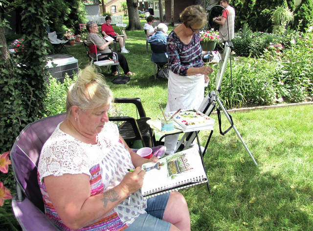 """One annual event of the Greenville Art Guild brings the artists to the home of Isabel Culbertson, of Greenville, for a """"Paint Out"""" or a plein air experience on her lawn, and lunch. About 15 artists attended the event Thursday, June 29. Pictured from left are Selena Burk, of Union City, Ohio, and Carol Peden, of Arcanum."""