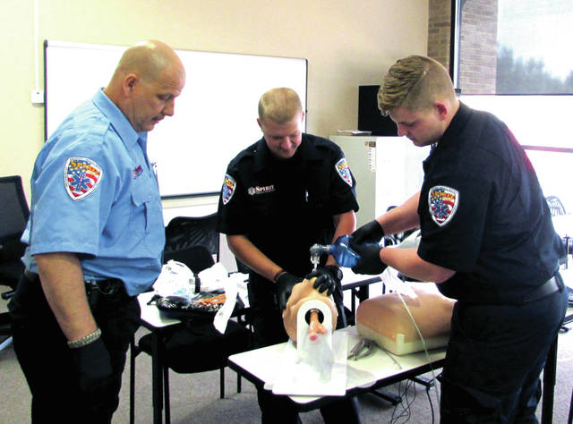 """Spirit employees pictured from left to right: Spirit Captain Charles Rock, Paramedic Justin Veverka and EMT Michael Wymer, practicing in a Spirit classroom on a rhythm generator. This gives experience in basic cardiac rhythm analysis. Captain Rock has been at Spirit nine years. """"I just love helping people,"""" he said."""