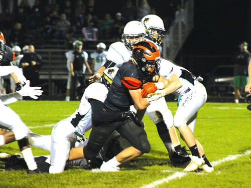Arcanum's Austin Fourman attempts to elude a swarm of Bee defenders. Bethel notched a 52-0 shutout against Arcanum.