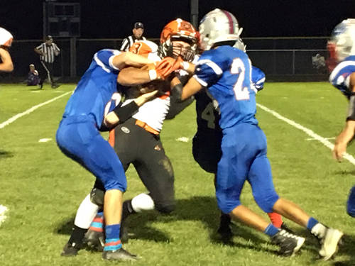 A group of Tri-Village defenders make a tackle during a Cross County Conference football game against Bradford on Friday in New Madison.