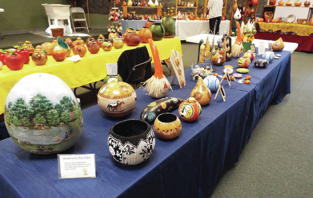 Various crafts made from gourds are displayed, including one depicting scenes from Greenville City Park.