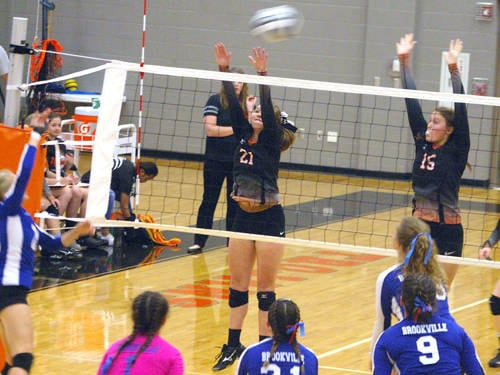 Arcanum's Grace Garno (21) and Trinity Layman (15) go up for a block during a volleyball match against Brookville on Monday in Arcanum.