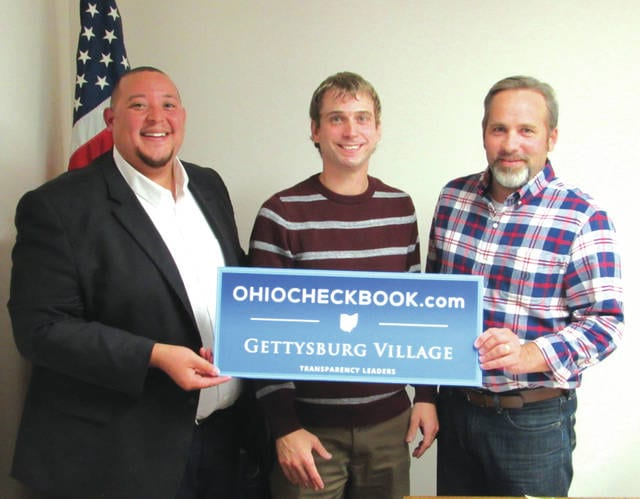 Josh Burton (left) congratulates Gettysburg Fiscal Officer Jesse Berry (center) and Gettysburg Mayor Jason Lance (right) as the Village of Gettysburg has chosen to participate in the state's OhioCheckbook.com program. All the village's financial transactions are now available for viewing online.