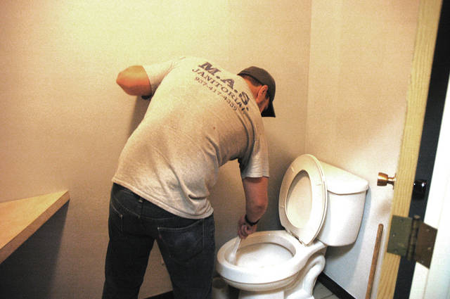 Jacob Donthnier, Operations Manager at M.A.S. Janitorial, cleans a restroom.