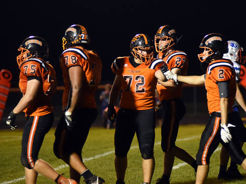 Ansonia's Austin Helmke (72) and Devyn Sink (2) celebrate during a Cross County Conference football game against Tri-Village on Oct. 20 in Ansonia.