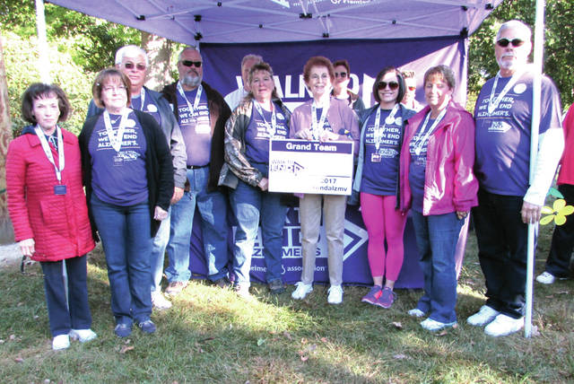 From left to right: Phyllis Campbell of Pitsburg, who raised a significant amount of donations this year; Deb Flatter, Dorthy Lentz's daughter-in-law, who serves on the group's advocacy committee; Bob Flatter, her son; Doug Downing, son-in-law; Becky Downing, daughter; Dorthy Lentz, team captain and Mission Chairman for the Greenville Walk to End Alzheimer's; Jennifer Flatter, her granddaughter; Brenda Flatter, daughter-in-law; and Mike Flatter, son. All raised at least $500 in donations to be named Champions. Bob, Mike and Doug sets up the buckets for the Flower Garden and the standees explaining what each color of flower represents. Bob, Mike and Becky work at Lewisburg Container. Becky ask The Container last year to print the standees, the company donated them. The boy pictured is my great nephew, Jasper Gains.