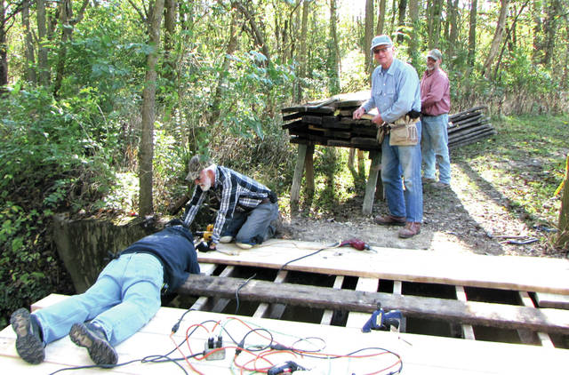 """Darke County Park District volunteers and """"Over-The-Hill-Gang"""" members: Ron Besecker, Larry Rench, Jim Poeppelman and Kevin Brunswick work re-decking a bridge at Shawnee Prairie Preserve and Nature Center, in Greenville."""