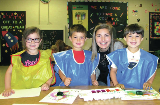 """The Greenville High School (GHS) Careers with Children students begin learning through the Greenville Learning Center, a preschool for children of ages three to five. Preschool students: Braydyn, Leenken and Kennedy, with Greenville High School Careers with Children Junior student Brooke Stachler. They are learning an activity: """"Painting with Ice."""""""