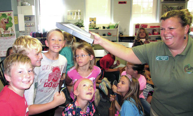 """Darke County Park District Naturalist Mandy Martin brought her favorite program """"Symbolic Migration"""" to the first, second and third-grade students of DeColores Montessori school, in Greenville, yesterday. Pictured at right, she is showing students the Monarch chrysalis."""