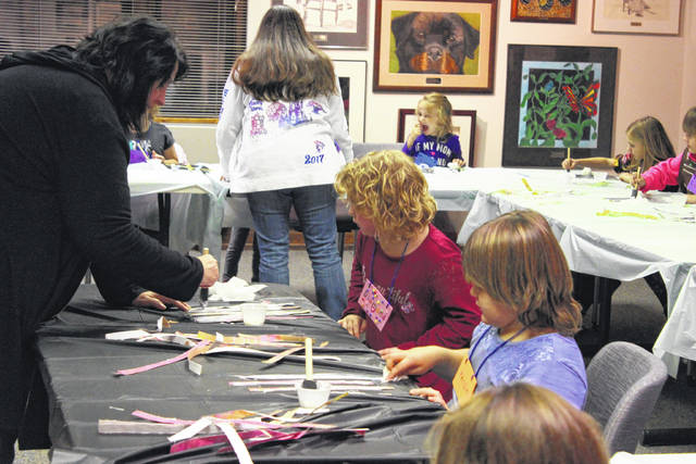 "Members of Girl Scout Brownie and Daisy Troop 30038 ""painted with paper"" at the DCCA workshop last Monday, earning their fine art badges while creating images of trees out of strips of colored paper."