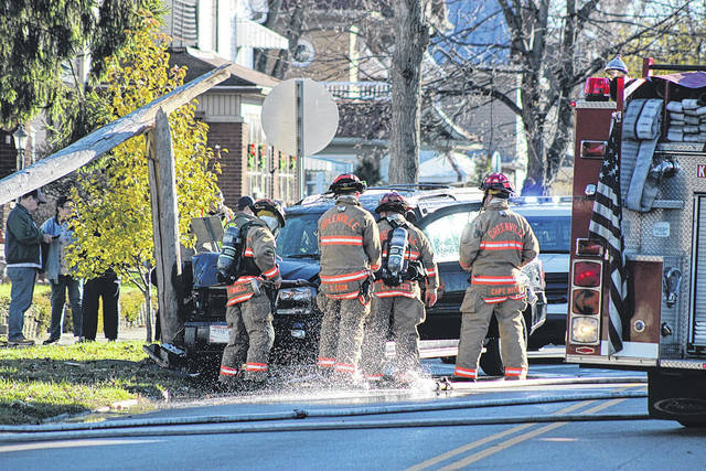 Greenville fire fighters inspect a vehicle which struck a light pole at the 500 block of Washington Avenue Tuesday afternoon. The vehicle was in flames upon their arrival and was quickly extinguished. Other first responders at the scene included Greenville Police and Greenville Township Rescue.