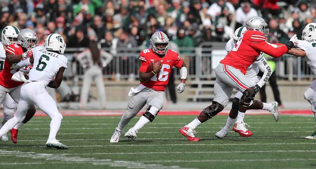 Ohio State four-year starter at quarterback J.T. Barrett runs with the ball during a 48-3 win over Michigan State. He is going for his fourth straight win against Michigan on Saturday.