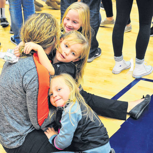 Versailles volleyball coach Kenzie Bruggeman (seated) celebrates the Lady Tigers' regional championship with nieces and nephew, Braden, Brinley, Harper, and Hadley Wourms, on Saturday afternoon at Fairmont High School's Trent Arena.