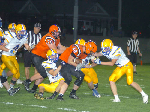 A group of Marion Local defenders tackle Versailles' Kurtis Rutschilling during a Midwest Athletic Conference football game on Sept. 22 in Versailles.