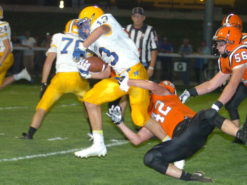 Versailles' Derek Cavin tries to tackle Marion Local's Nolan Habodasz during a Midwest Athletic Conference football game on Sept. 22 in Versailles.