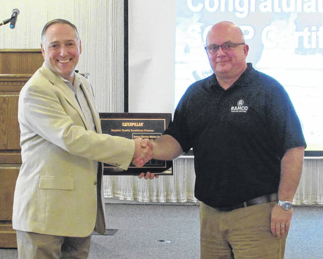 """Caterpillar Supplier Development Engineer Bart Preston presents Ramco Quality Manager David Warner with a plaque in recognition of Ramco Electric Motors achieving the """"silver level"""" of Caterpillar's Supplier Quality Excellence Process."""