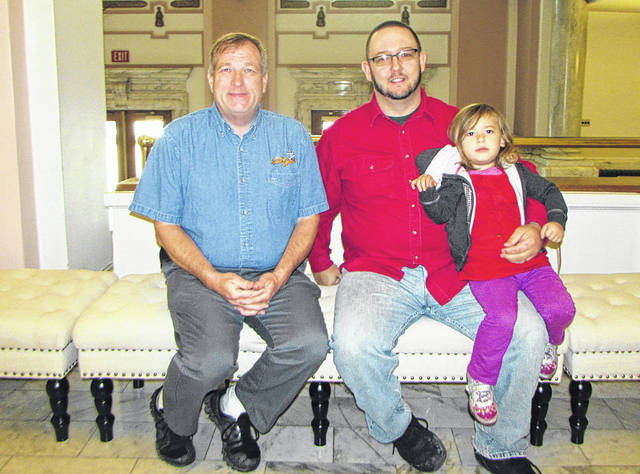 Ron Asman, of Greenville, is a private contractor serving as resident technician at St. Clair Memorial Hall. He has been purchasing benches for the hall out of his own pocket. He and Justin Thomas Ord, also of Greenville, have started a fundraiser to purchase more benches. Pictured from left to right: Ron Asman, Justin Thomas Ord and Justin's daughter Wynter, sitting on one of the benches in the hall.