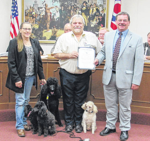 Susan and Mike Brown (left) receive a certificate of commendation from Greenville Mayor Steve Willman (right). The city wished to congratulate two of the Brown's therapy dogs — John Coffey and Harley — for their work providing cheer and comfort to local residents. Shown as well are Brittany and Mya, also in training to be therapy dogs.
